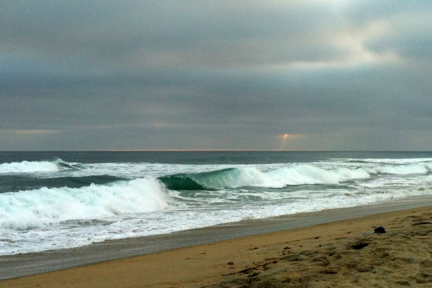 Green wave and distant beam of sunlight.